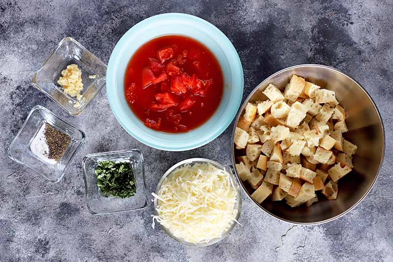 Horizontal image of a bowl of red sauce, shredded cheese, bread cubes, and seasonings.