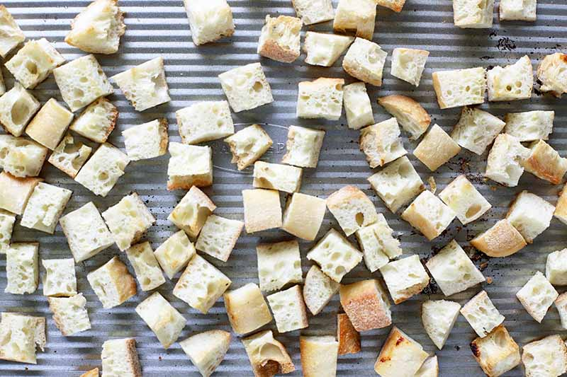 Horizontal image of cubes of bread on a sheet pan.