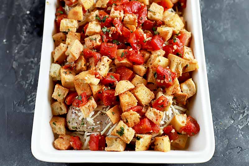Horizontal image of an unbaked casserole entree topped with cubes of bread, red vegetables, and herbs.