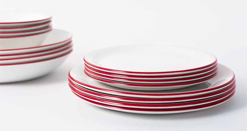 Horizontal image of stacked white dishes in two sizes with a red trim.