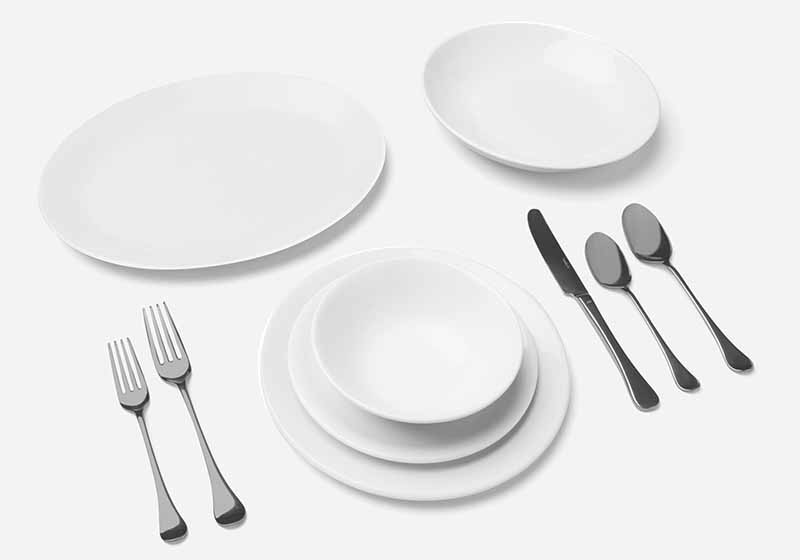 Horizontal image of silverware, a large platter, and assorted dishes.
