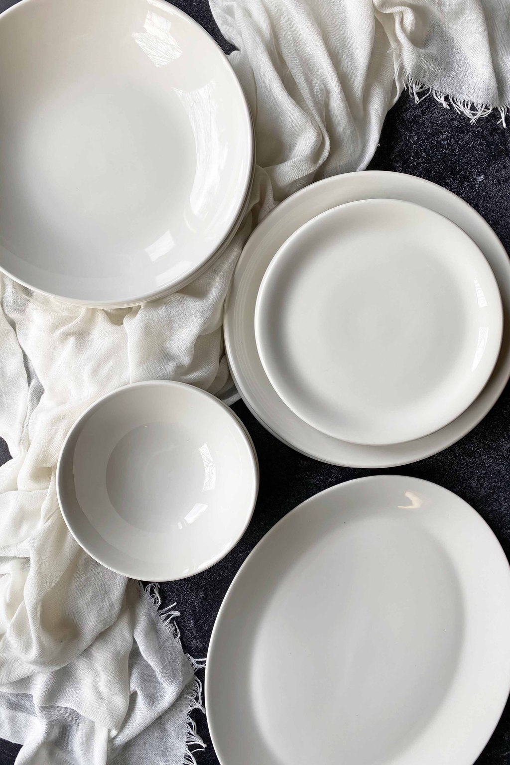 Vertical top-down image of assorted white dishes on a dark surface on a white towel.