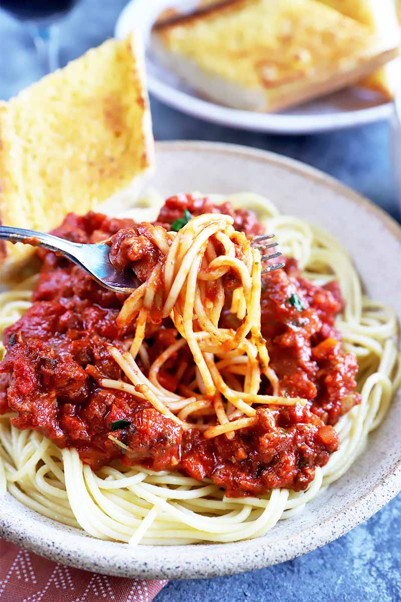 Vertical image of a forkful of pasta in a bolognese on a plate next to toasted garlic bread.
