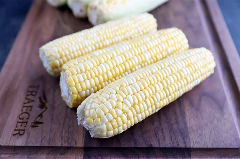 Horizontal image of three cleaned ears of corn on a wooden cutting board.