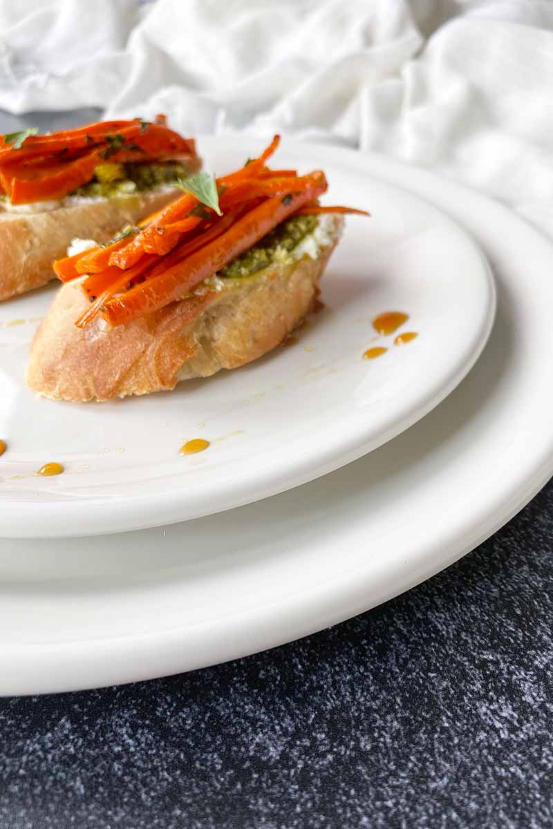 Vertical image of carrot crostini on top of two white dishes on a dark surface.