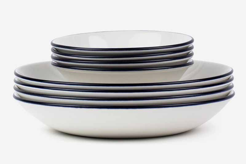 Horizontal image of two sizes of stacked bowls with a navy trim.