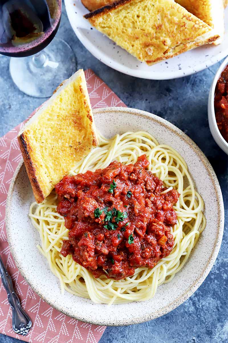 Vertical top-down image of a plate of pasta with a chunky tomato sauce and a slice of garlic bread on a red napkin next to a fork and more sauce in a bowl.