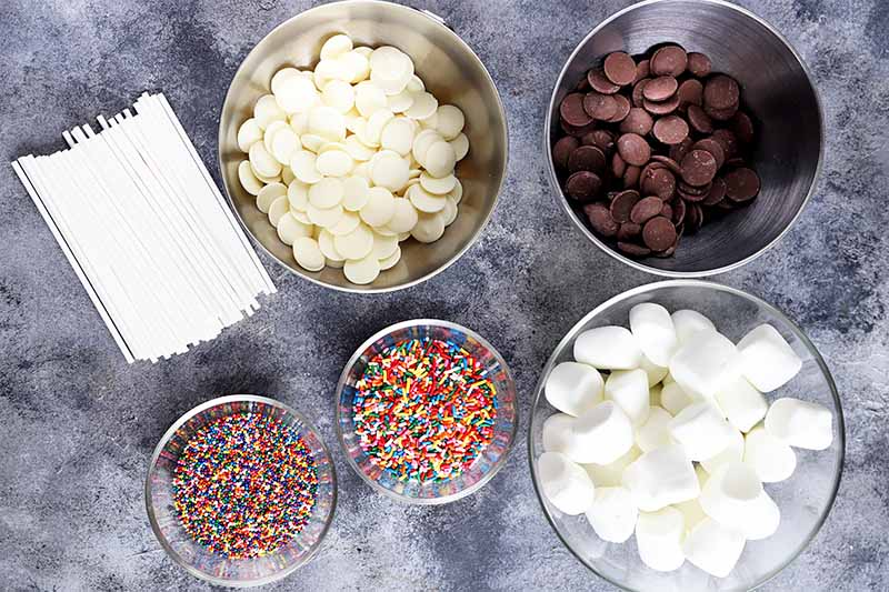 Horizontal image of assorted candies and candy wafers and white sticks on a gray surface.