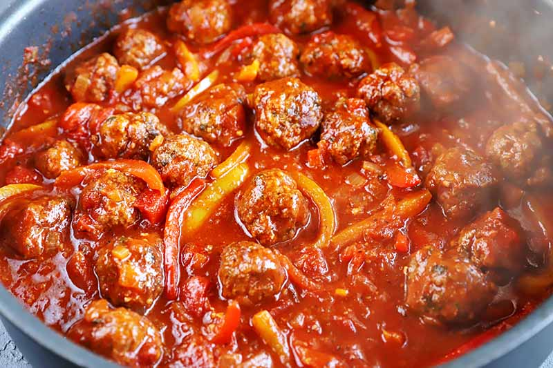 Horizontal image of a steaming pot of tomato and bell pepper sauce mixed with mounds of ground beef.