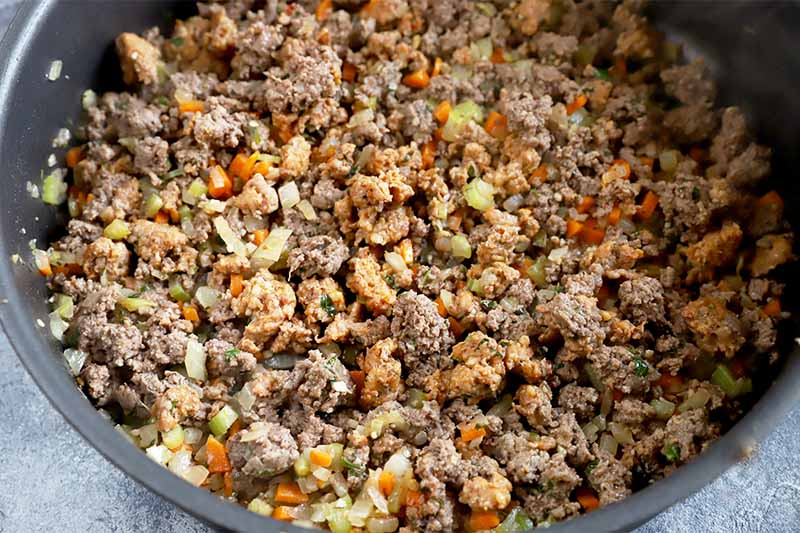 Horizontal image of cooking ground meat and sausage with seasonings in a pan.