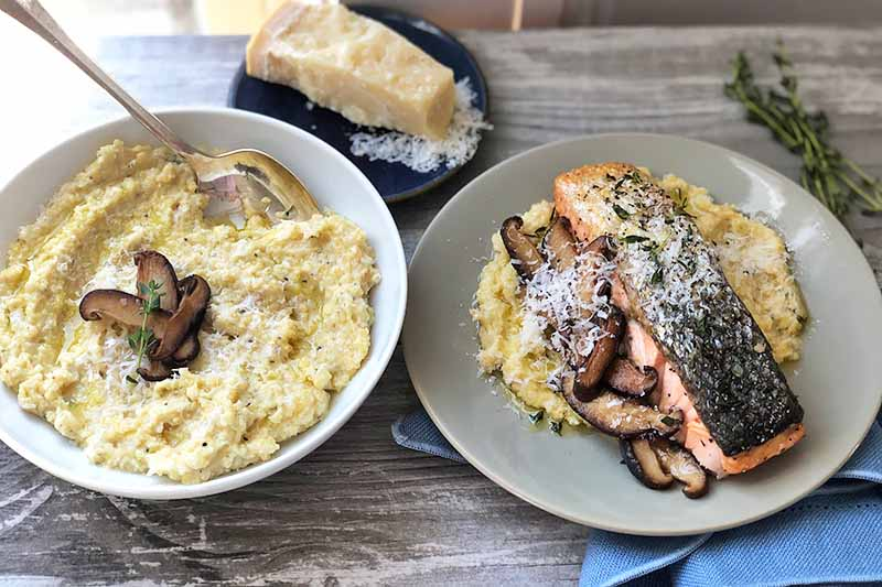 Horizontal image of a bowl of grits next to a gray plate with a piece of cooked fish and mushrooms next to a small plate with parmesan.