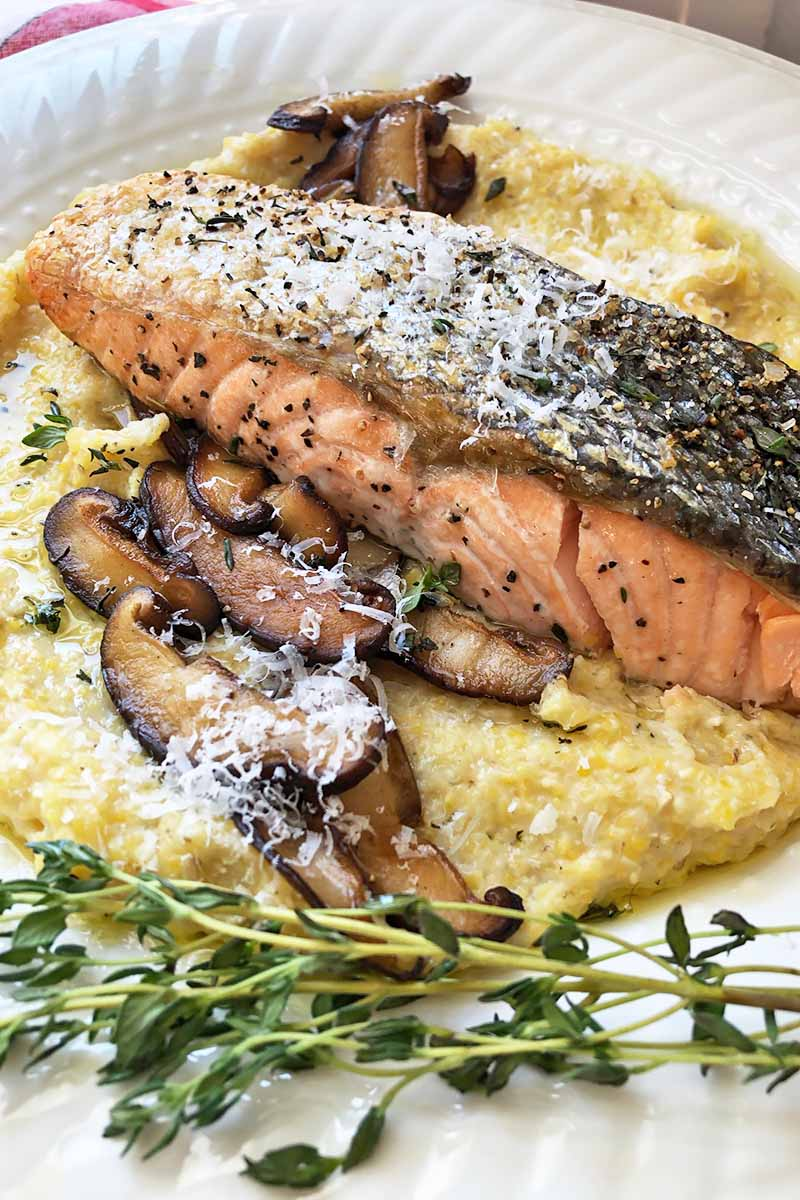 Vertical close-up image of a cooked fillet of salmon over grits and shiitake slices next to thyme leaves on a white plate.