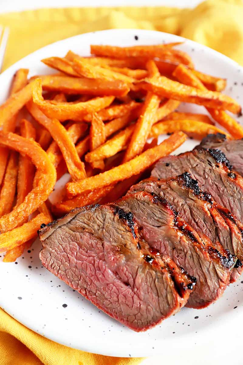 Vertical image of sweet potato fries and slices of meat on a white plate.