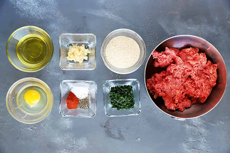 Horizontal image of prepped ingredients in glass bowls and a bowl of raw ground beef on a gray surface.