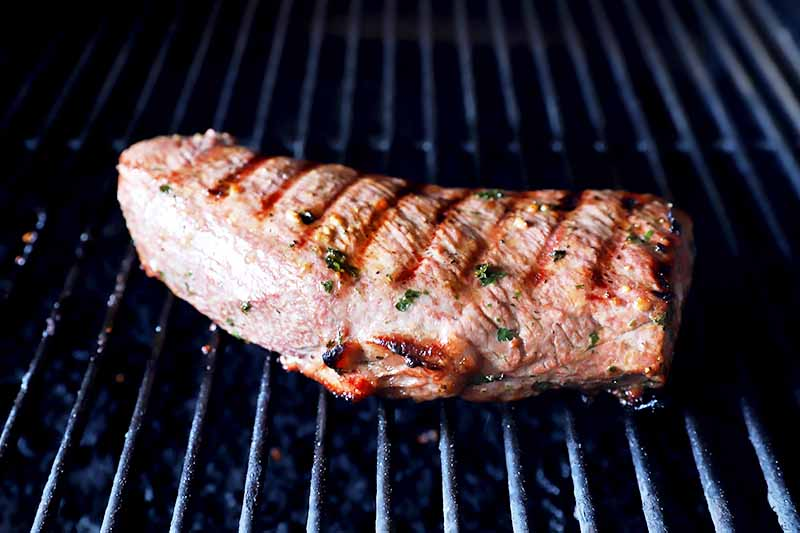 Horizontal of a large piece of meat with herbs cooking on a grill.