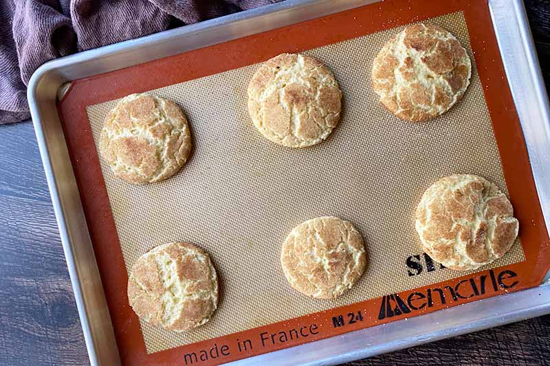 Horizontal image of 6 baked cookies on a tray lined with a silicone mat.