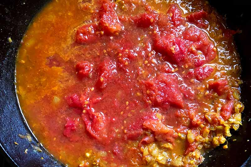 Horizontal image of cooking tomatoes and sauteed spiced onions in a skillet.