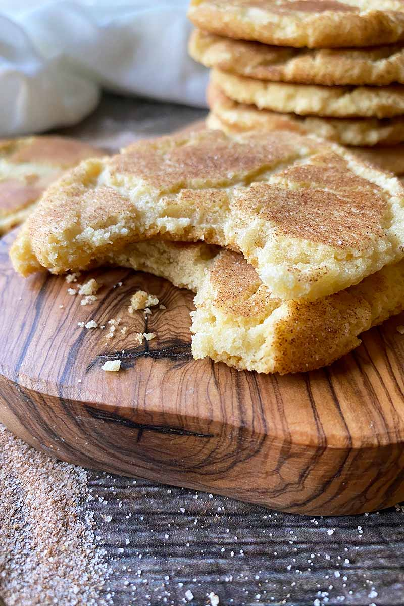 Vertical close-up image of half-eaten cookies with a spice coating on a wooden board.