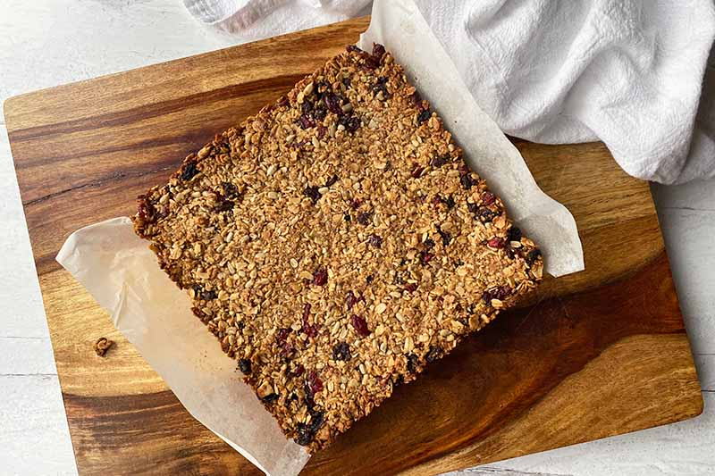 Horizontal image of a baked good in the shape of a square with parchment paper on the bottom.