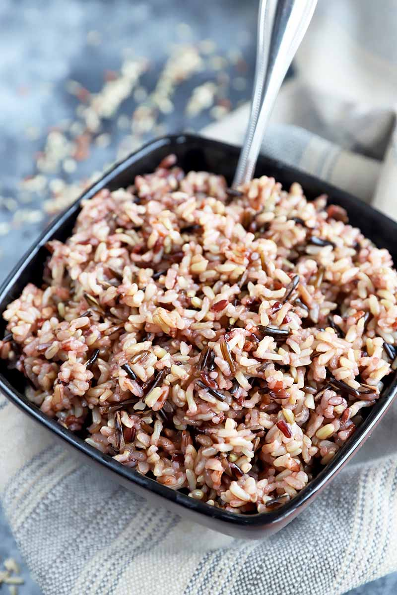 Vertical close-up image of a large brown bowl filled with cooked wild rice on a towel with a spoon inserted into the bowl.