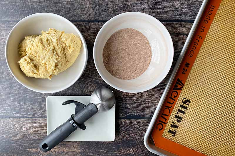 Horizontal image of a bowl of thick batter, a bowl of a cinnamon sugar mixture, a plate with an ice cream scooper, and a tray lined with a silicone mat.