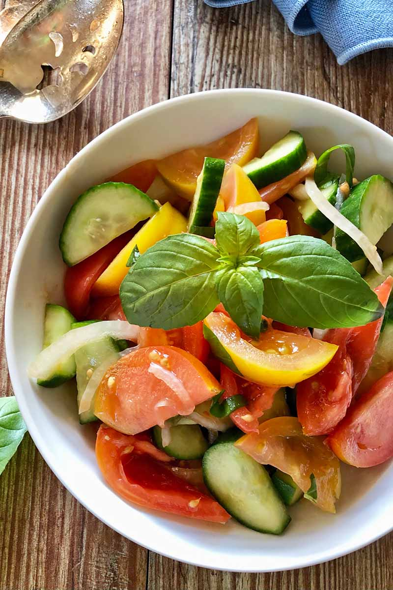Vertical image of a white bowl with slices of mixed summer vegetables topped with basil leaves on a wooden table.