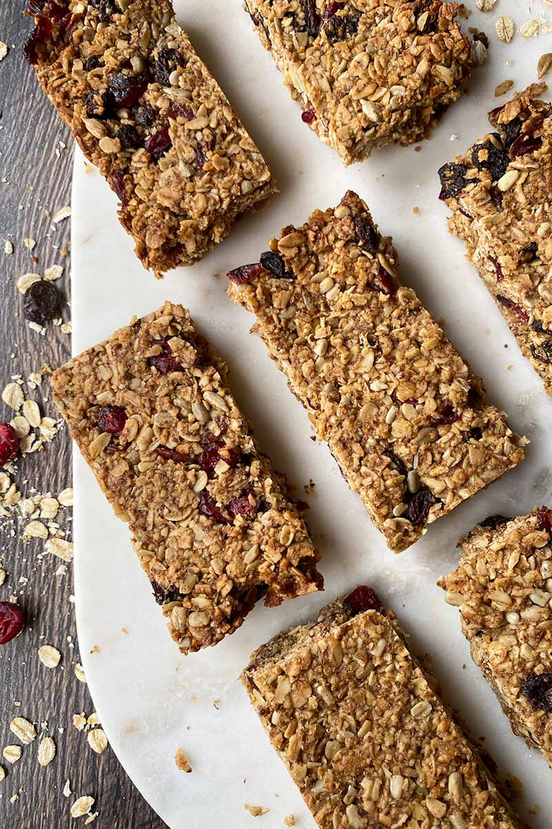 Vertical top-down image of rows of granola bars on a white cutting board.