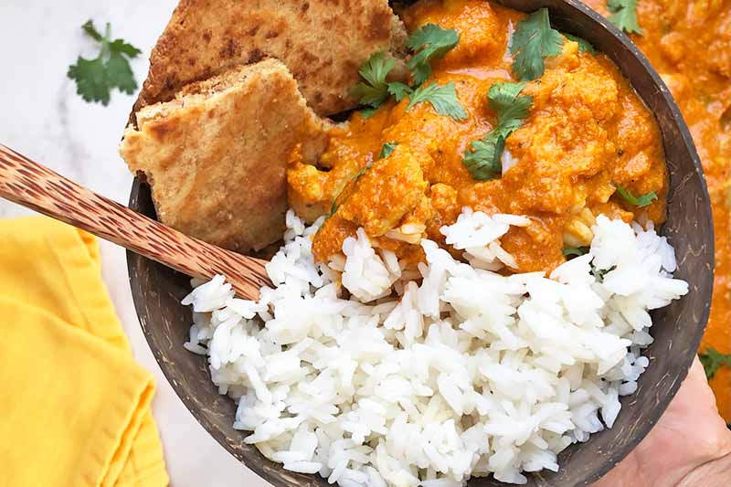 Horizontal top-down image of a brown bowl filled with rice, stew, and slices of flatbread with a spoon on a yellow towel.