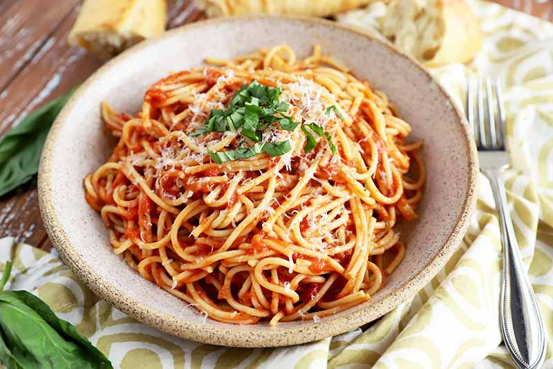 Horizontal image of a bowl filled with noodles in tomato sauce with herb and cheese garnish next to a fork and towel.