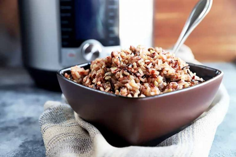 Horizontal image of cooked grains in a brown bowl on a towel with a spoon inserted into the bowl.