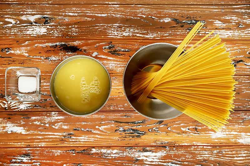 Horizontal image of uncooked noodles, broth, and salt in dishes on a wooden surface.