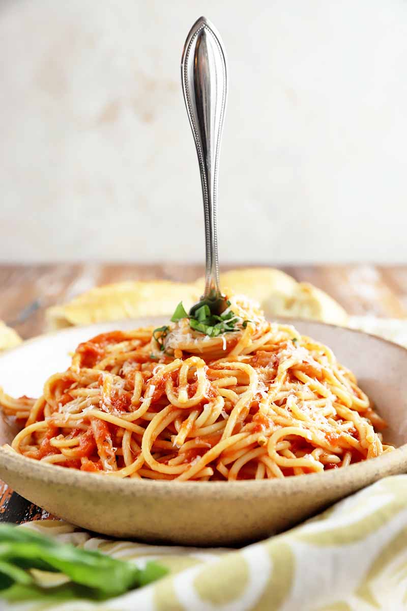 Vertical image of a bowl of noodles mixed with tomato sauce on a towel with a fork inserted upright.
