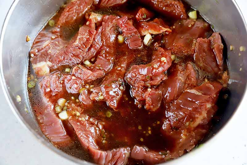 Horizontal image of marinating raw slices of meat in a bowl.