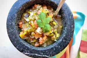 Horizontal image of a stone bowl filled with chopped vegetables topped with a fresh herb and a spoon inserted into it.