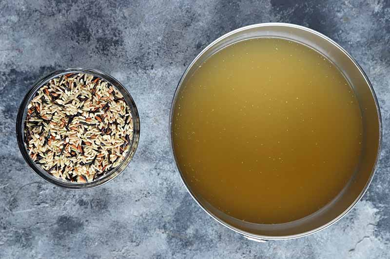 Horizontal image of a bowl of uncooked assorted grains and a bowl of chicken stock.