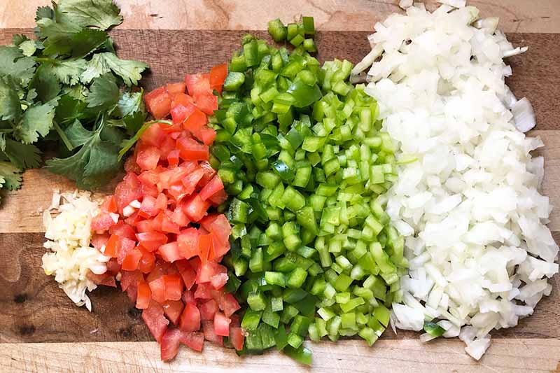 Horizontal image of chopped vegetables and herbs in neat rows on a wooden cutting board.