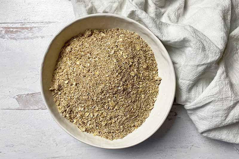 Horizontal image of a large white bowl filled with partially pulverized dry ingredients.