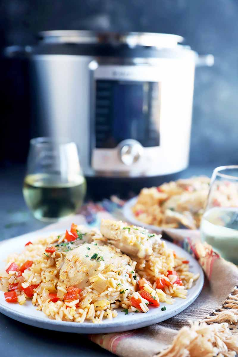 Vertical image of two plates with cooked rice, vegetables, and chicken next to a large appliance, napkins, and a glass of white wine.