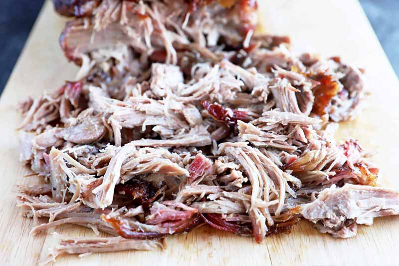 Horizontal image of shredded cooked meat on a wooden cutting board.