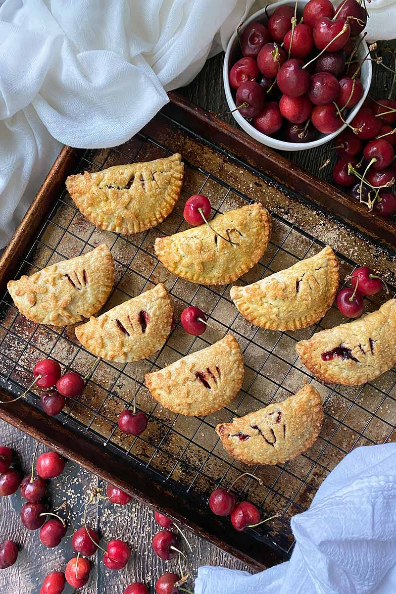 Vertical top-down image of two rows of half-moon stuffed pies on a cooling rack on a baking sheet next to cherries.
