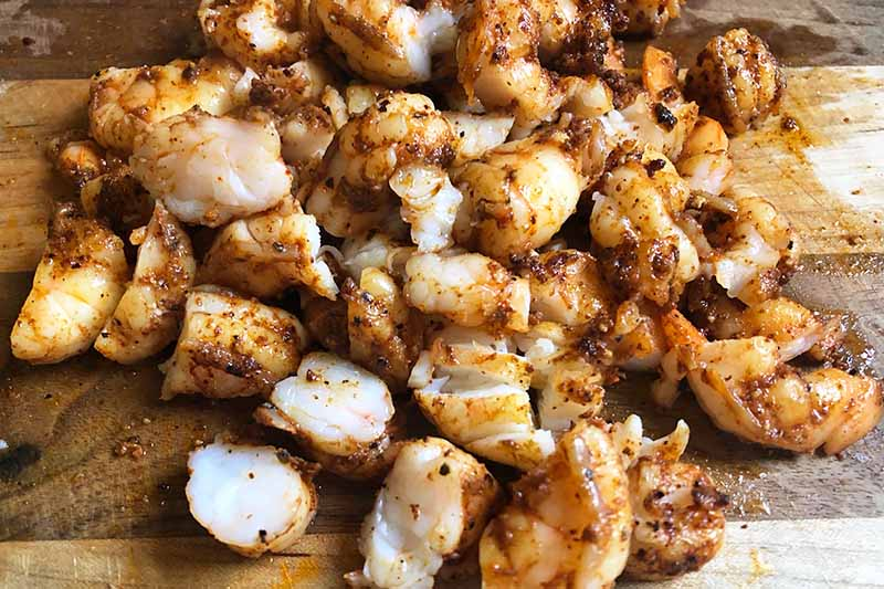 Horizontal image of chopped seasoned and cooked seafood.
