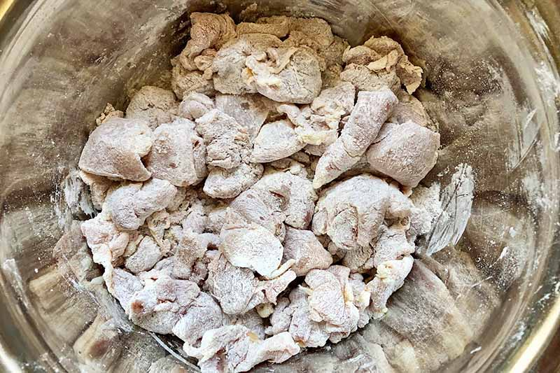 Horizontal image of dredged raw poultry chunks in a metal bowl.