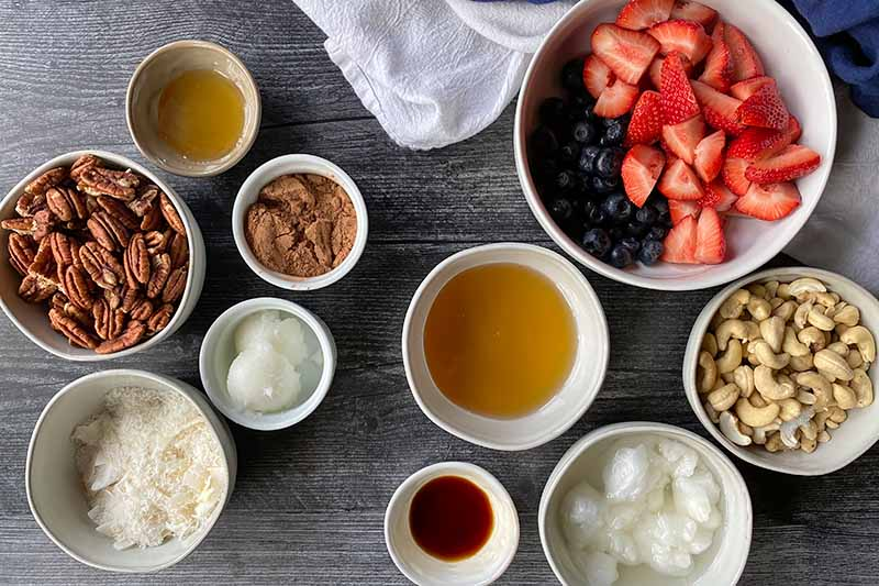 Horizontal image of assorted measured ingredients in white bowls on a black surface.
