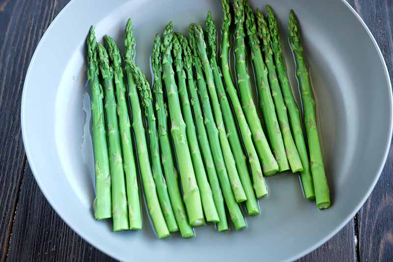 Horizontal image of steaming green vegetables spears in a pan with water.