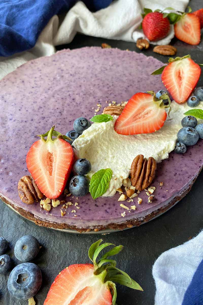 Vertical image of a flat, round purple dessert garnished with sliced fruit, nuts, mint, and whipped cream.