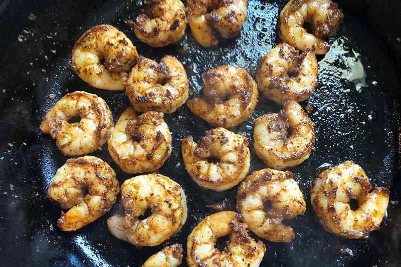 Horizontal image of cooked whole seasoned shrimp in a cast iron skillet.