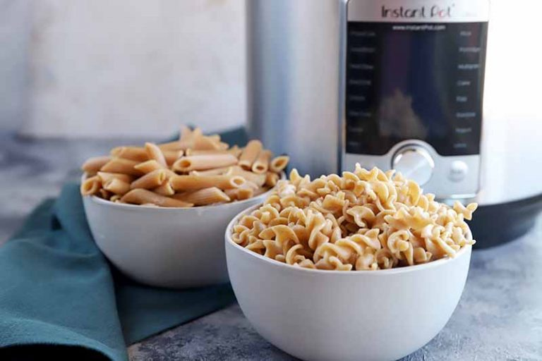 Horizontal image of two small white bowls filled with cooked penne and corkscrews next to a towel and a kitchen appliance.