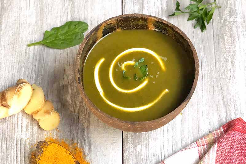 Horizontal image of a wooden bowl filled with a dark green soup drizzled with sour cream and garnished with fresh herbs.