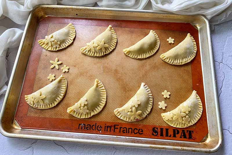 Horizontal image of unbaked half-moon pastries with decorations on a baking sheet.