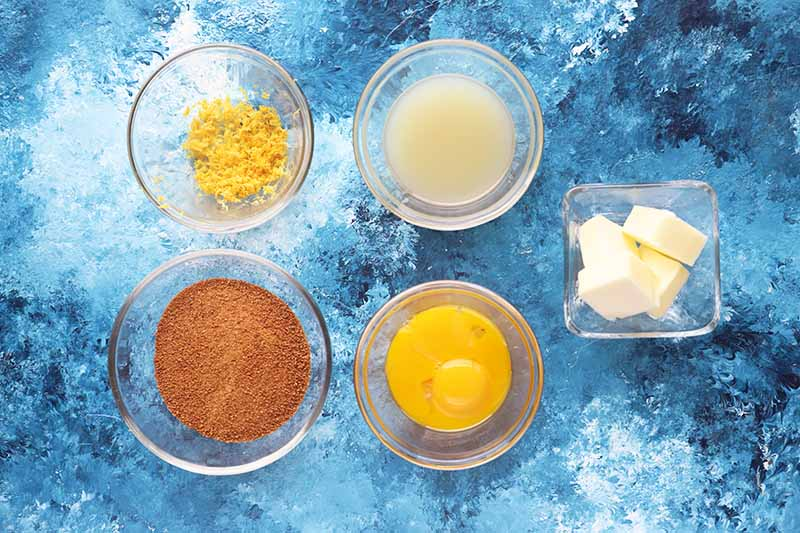 Horizontal image of zest, sugar, lemon juice, yolks, and butter in small glass bowls.